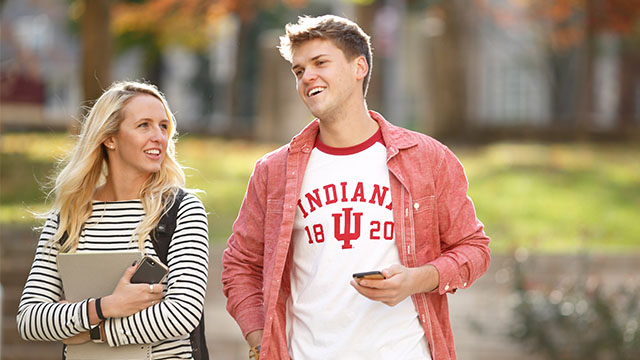 Students walking on campus with electronic devices